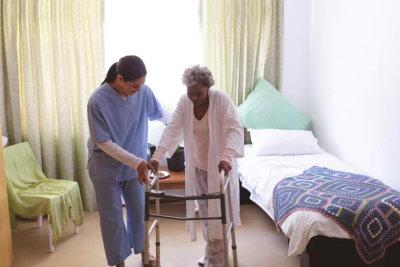woman guiding a senior woman to walk