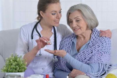 nurse giving a senior woman a medicine