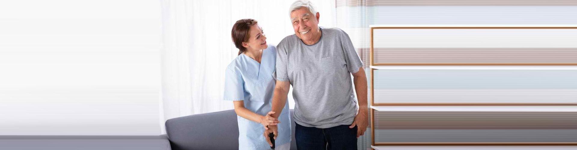 caregiver guiding a man to walk