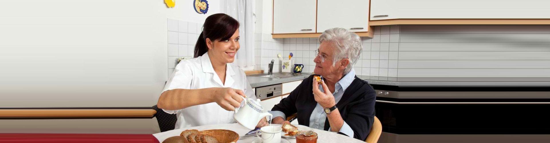 caregiver preparing food for senior woman
